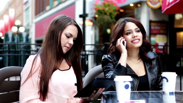 Two young women talking at outdoor cafe video