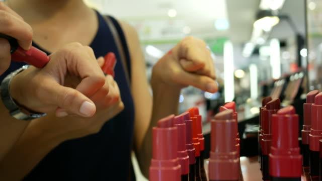zwei junge frauen testen lippenstift im store - kosmetik stock-videos und b-roll-filmmaterial