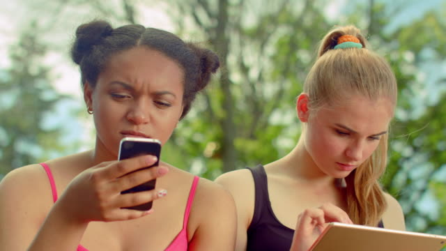 Two young women using digital devices. Digital lifestyle. Mobile technology video