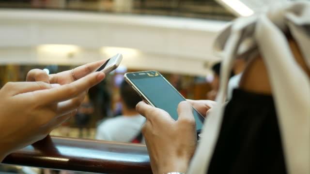 Duas mulheres jovens usando telefone em shopping center - vídeo