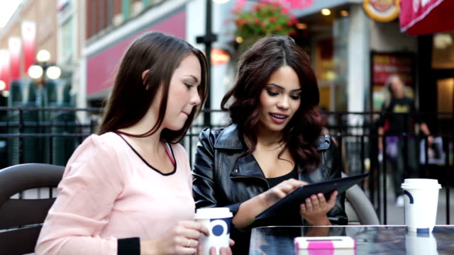Two young women with digital tablet at outdoor cafe video