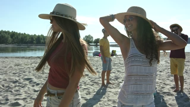 Two young women with hat enjoying time on river beach. video