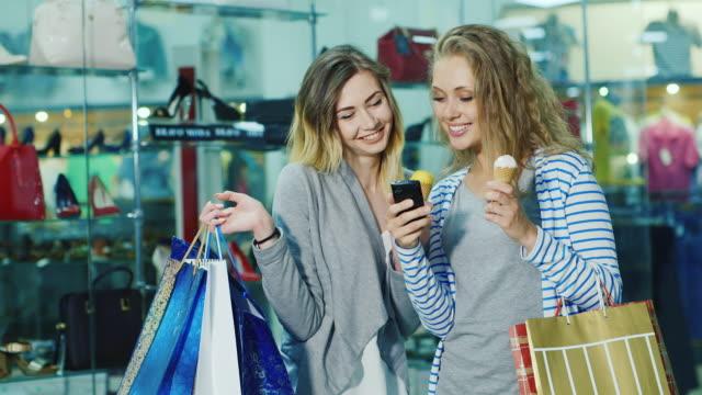 två unga kvinnor med shoppingkassar dyal gå glass och överväga något på telefonen - köpnarkoman bildbanksvideor och videomaterial från bakom kulisserna