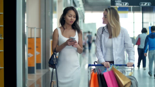 vídeos de stock e filmes b-roll de two young women with shopping cart using smartphone and talking - online shopping