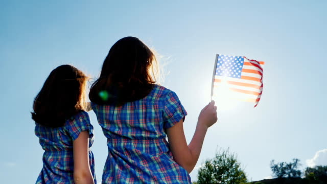 Two young women with the American flag. In the rays of the sun against the sky. Rear view. independence Day Two redheaded teenage girls with an American flag. Smile, look at the camera. 4K slow motion video family 4th of july stock videos & royalty-free footage