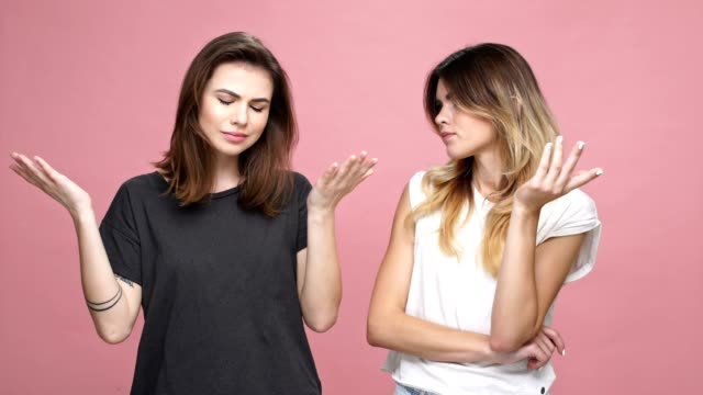 Two young worried women thinking what to do and shrugging shoulder while standing isolated over pink background Two young worried women thinking what to do and shrugging shoulder while standing isolated over pink background faq stock videos & royalty-free footage