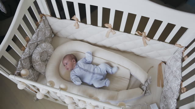 two-month baby boy in blue baby sliders is lying in the crib at home in bedroom. baby boy trying to fall asleep in cot. baby boy - 0 11 mesi video stock e b–roll