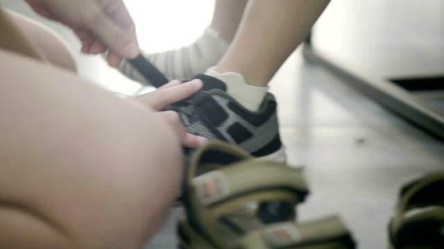 связывание шнурка сына - обувь стоковые видео и кадры b-roll