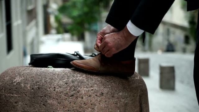 Tying Lace Tying lace on the way to work in Istanbul streets. dress shoe stock videos & royalty-free footage