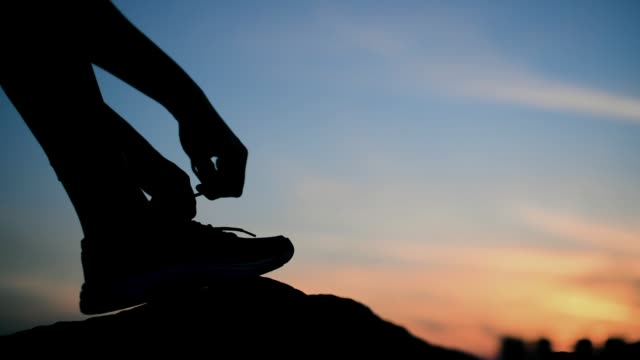 Tying sports shoes on a blue and yellow vibrant sunset sky background.