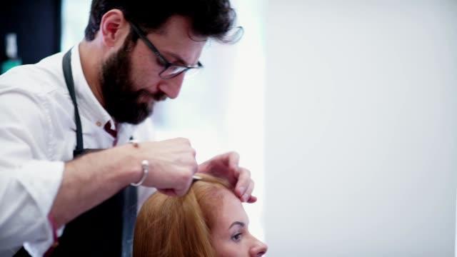 tylist-hairdresser at work. Man hairdresser makes hair parting video