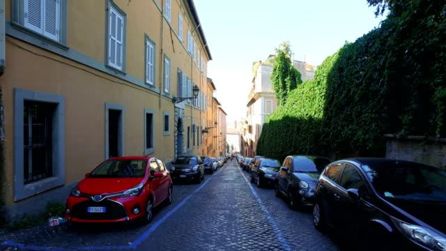 Typical dark italian narrow street with parked car vehicles
