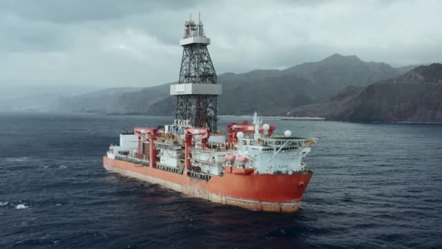 Typical drill ship for exploration, drilling and production of oil and gas from offshore fields Drilling vessel exploring new oil and gas fields in the ocean crane construction machinery stock videos & royalty-free footage