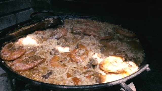Typical Spanish rice paella cooked with natural fire Cooking Spanish paella, a famous typical spanish rice dish. Close up shoot arthropod stock videos & royalty-free footage