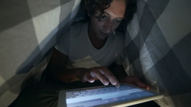 Typing a message under the blanket. video