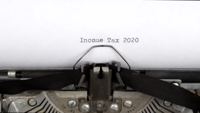 Typing a text income tax 2020 close-up view. Old vintage typewriter with a white empty sheet of paper. Concept of finance, paperwork and bookkeeping Typing a text income tax 2020 close-up view. Old vintage typewriter with a white empty sheet of paper. Concept of finance, paperwork and bookkeeping typewriter stock videos & royalty-free footage