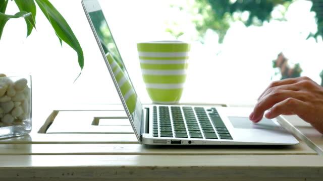 vídeos de stock, filmes e b-roll de computador portátil de digitação na tabela de madeira com luz de beleza natural como pano de fundo - blogar