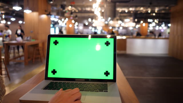 Typing laptop keyboard with green screen monitor
