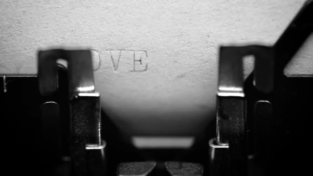 typing love word with an old typewriter - love video stock e b–roll