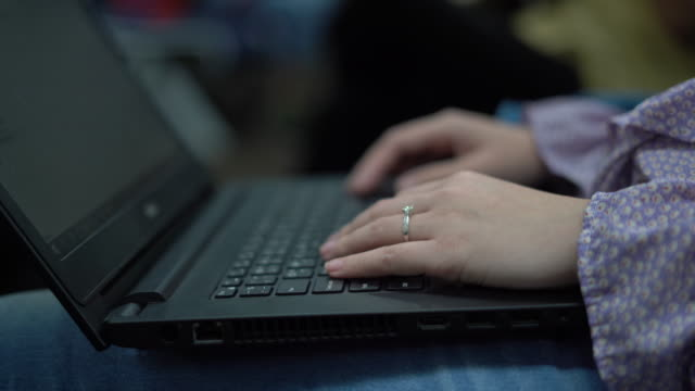 Typing on laptop. Tidy fit businesswoman  using laptop for work and having diamond ring on ring finger