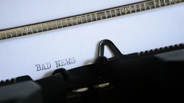 att skriva uttrycket dåliga nyheter med en gammal manuell skrivmaskin - paper mass bildbanksvideor och videomaterial från bakom kulisserna