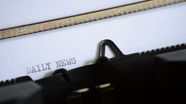 att skriva uttrycket daily news med en gammal manuell skrivmaskin - paper mass bildbanksvideor och videomaterial från bakom kulisserna