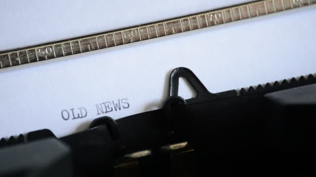 att skriva uttrycket gamla nyheter med en gammal manuell skrivmaskin - paper mass bildbanksvideor och videomaterial från bakom kulisserna