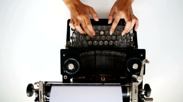 Typing with retro typewriter High angle view of secretary prints on vintage typing machine. typewriter stock videos & royalty-free footage