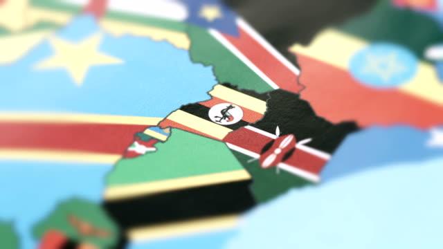 uganda borders with national flag on world map - линия экватора стоковые видео и кадры b-roll