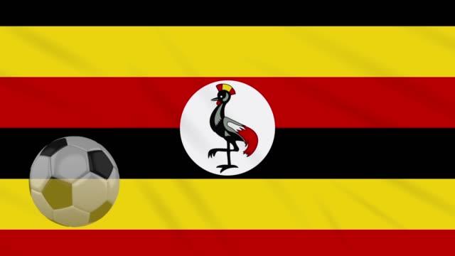 Uganda flag waving and soccer ball rotates, loop Uganda flag and soccer ball rotates against background of a waving cloth, loop international match stock videos & royalty-free footage