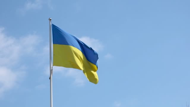 Ukrainian flag on a wind on a blue cloudy sky background at sunny day.