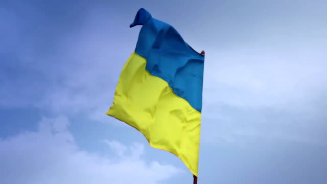 Ukrainian national flag waving on flagpole in blue sky. Ukraine video