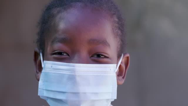 ultra närbild porträtt bild av en ung svart afrikansk flicka bär en ansiktsmask under lockdown för att förhindra covid-19 coronavirus pandemi, sydafrika - face mask bildbanksvideor och videomaterial från bakom kulisserna