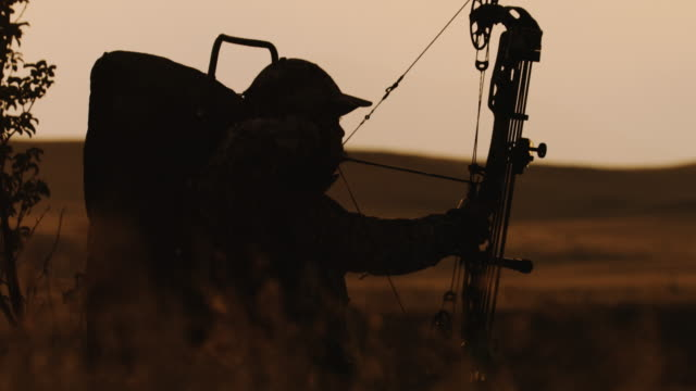 ultra slow motion, 150 frames per second, of a backlit bowhunter draws his bow, aims and fires at his target in the beautiful sunset life. - cacciatore video stock e b–roll