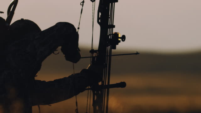 Ultra slow motion, 200 frames per second, of a backlit bowhunter drawing back his bow in the beautiful sunset life. video