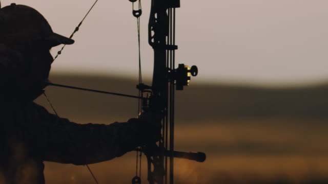 Ultra slow motion, 200 frames per second, of a backlit bowhunter firing his bow at his target in the beautiful sunset life. video