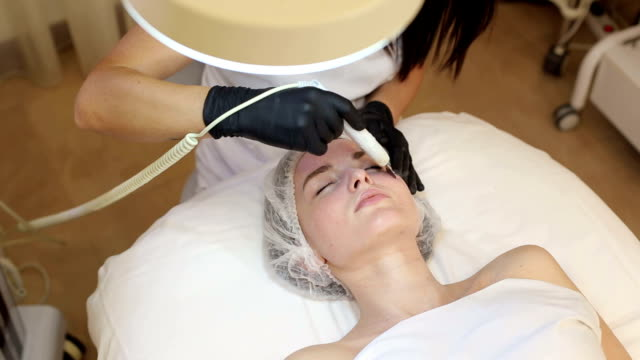Ultrasonic face cleaning, peeling, in a beauty salon. Ultrasonic face cleaning, peeling, in a beauty salon. Woman receiving cleansing therapy with a professional ultrasonic equipment in cosmetology office. beautician stock videos & royalty-free footage
