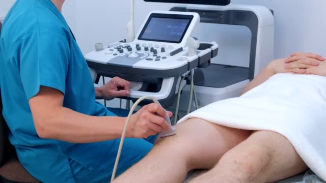 Ultrasound screening of knee joint for man using ultrasound scanner in clinic. video