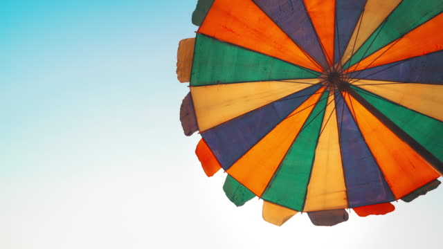 Umbrella on sand beach with blue sky background