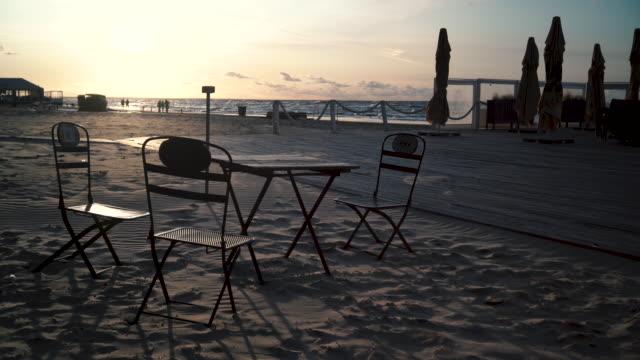 regenschirme auf der terrasse bei starkem wind - ostsee stock-videos und b-roll-filmmaterial