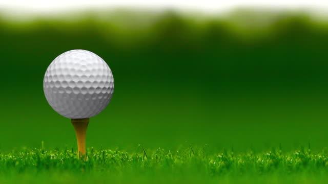vidéos et rushes de bille de golf sans marque tournant sur un tee de golf sur un fond de bokeh - boucle sans couture - golf
