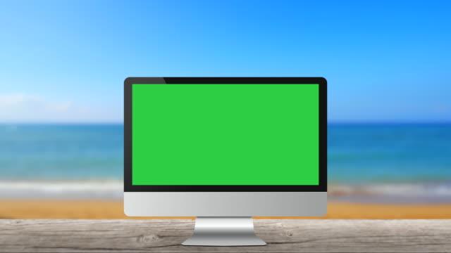 vídeos de stock, filmes e b-roll de monitor de computador modernos sem marca na praia mar fundo tela verde em branco - poster