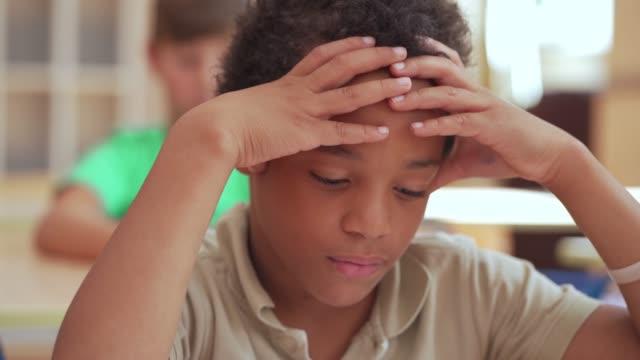 stockvideo's en b-roll-footage met onzekere basisschooljongen die het examen in school bekijkt terwijl het houden aan zijn hoofd - schooljongen