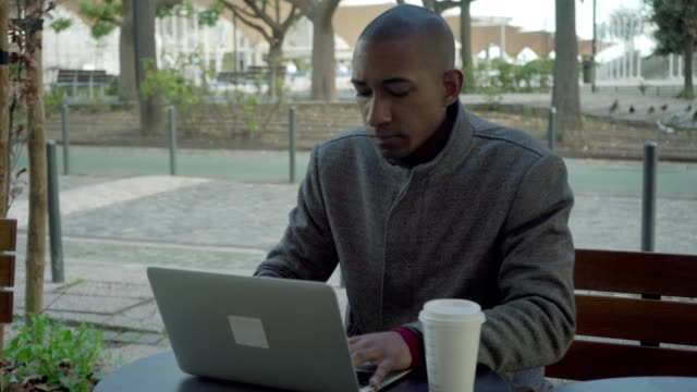 vídeos de stock e filmes b-roll de uncertain young man using laptop outdoor - esplanada portugal