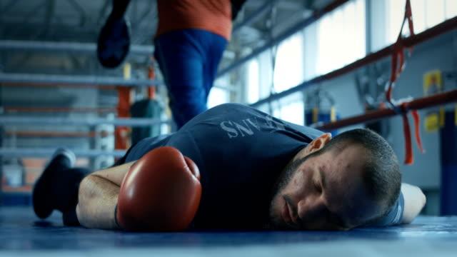unconscious boxer in gloves lying on ring - спортсмен стоковые видео и кадры b-roll