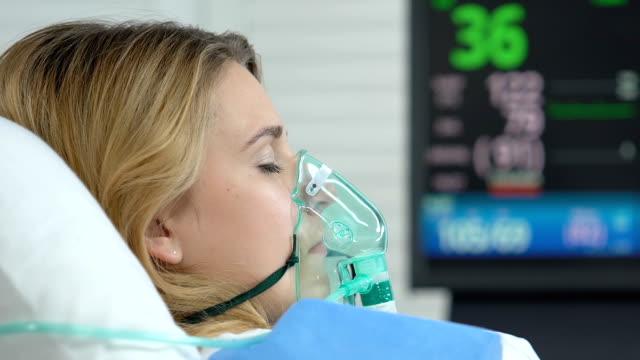medvetslös sjuk kvinna liggande säng, hjärtfrekvens skylt försvinnande sjukhus monitor - kvinna ventilationssystem bildbanksvideor och videomaterial från bakom kulisserna