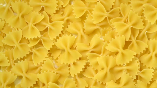 Uncooked farfalle or bow-tie pasta rotating top view Uncooked farfalle or bow-tie pasta rotating top view uncooked pasta stock videos & royalty-free footage