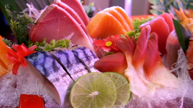 Uncooked fresh salmon and red tuna fish and saba and squid and crab with vegetable and fruits set pieces served video