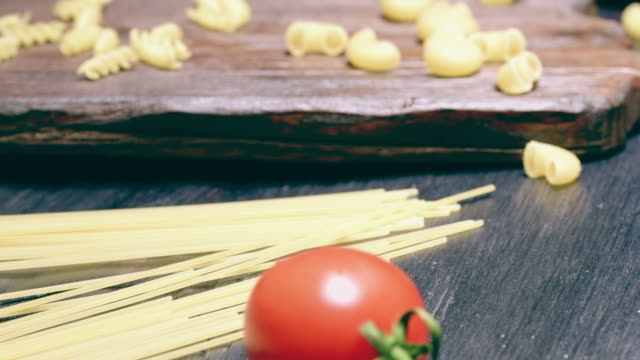 Uncooked pasta and tomato Dry pasta and cherry tomatoes on dark wood cutting board and on black table. Angle close-up view. Sliding motion uncooked pasta stock videos & royalty-free footage