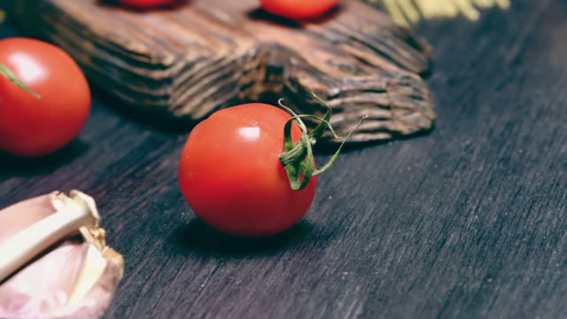 Uncooked pasta and tomato Sliced and whole red cherry tomatoes with spices and uncooked pasta on dark wood cutting board and on black table. Close-up uncooked pasta stock videos & royalty-free footage